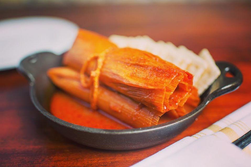 tres tamales en una sartén de hierro fundido con salsa y galletas saladas