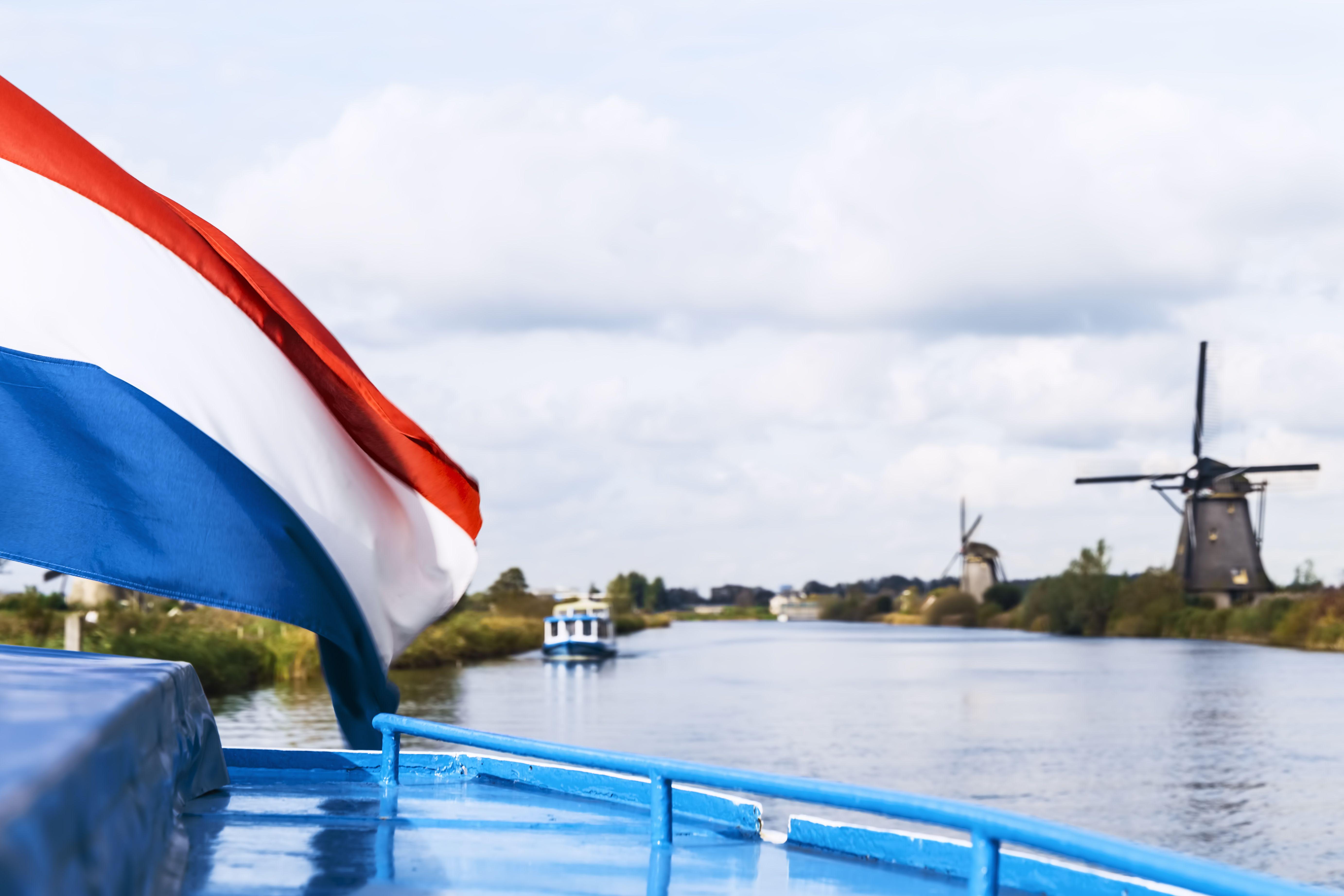 Dutch Flag Waving In The Wind Against Windmills, Kinderdijk, Netherlands