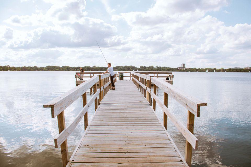 Un muelle que se extiende hacia las aguas del lago Calhoun con una persona pescando al final del mismo