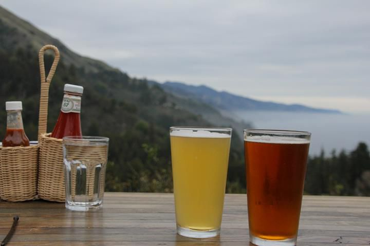 two glasses of beer (one pale and one amber-colored) on a table with smaller glass of water and a basket with ketchup and hotsauce. There is a veiew of a tree-covered mountain and the ocean in the background