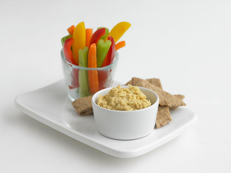 Tazón de hummus, palitos de pimientos, zanahoria y apio en vidrio, con pan de pita en la bandeja