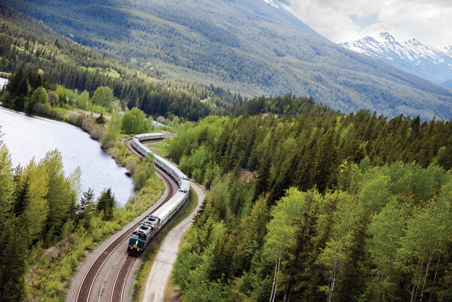 A train coming down the tracks through the mountains around a lake