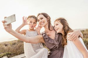 mom taking travel selfie with daughters