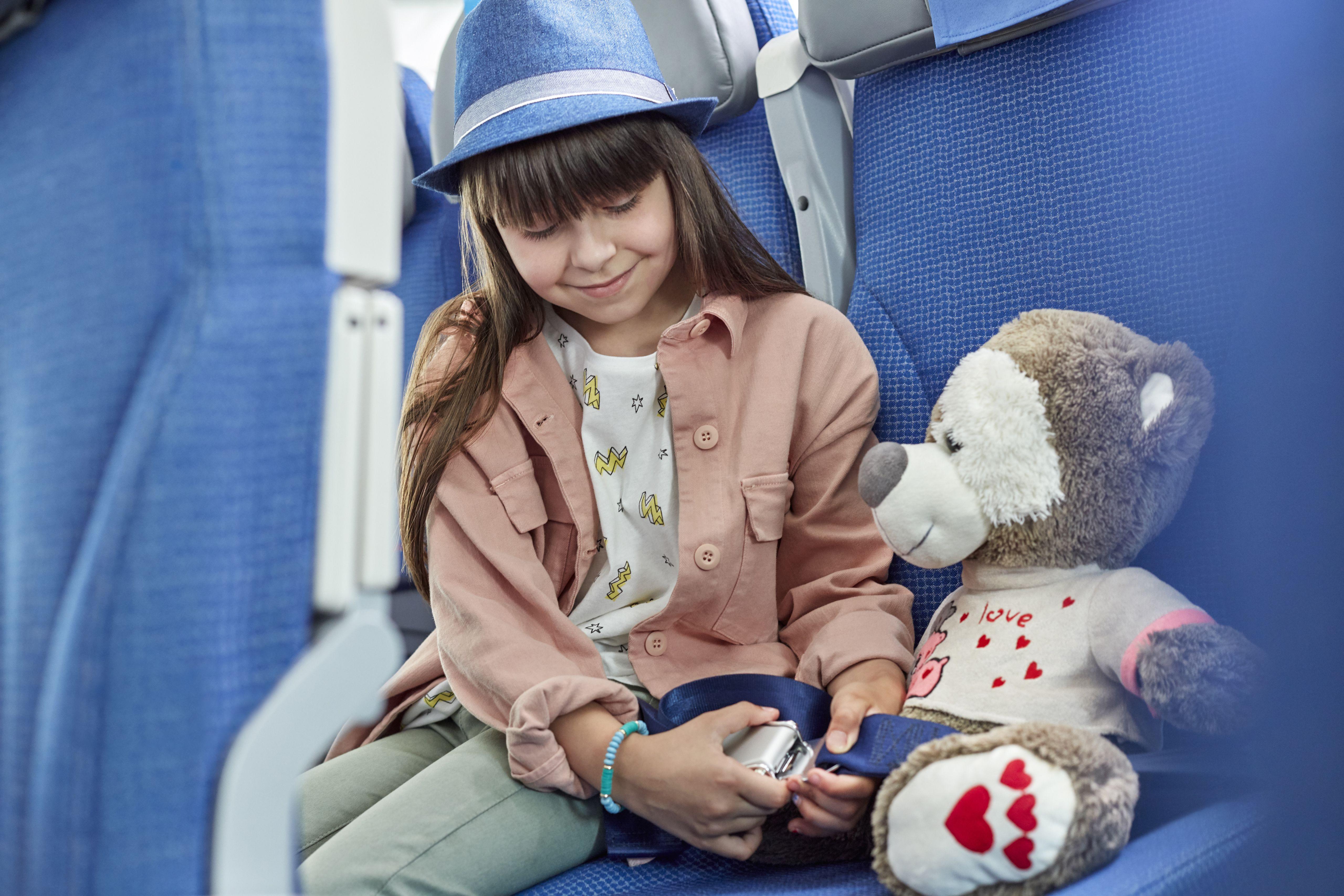 Girl fastening seat belt on stuffed animal on airplane