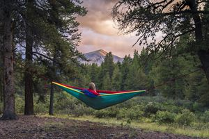 Woman resting in hammock at forest
