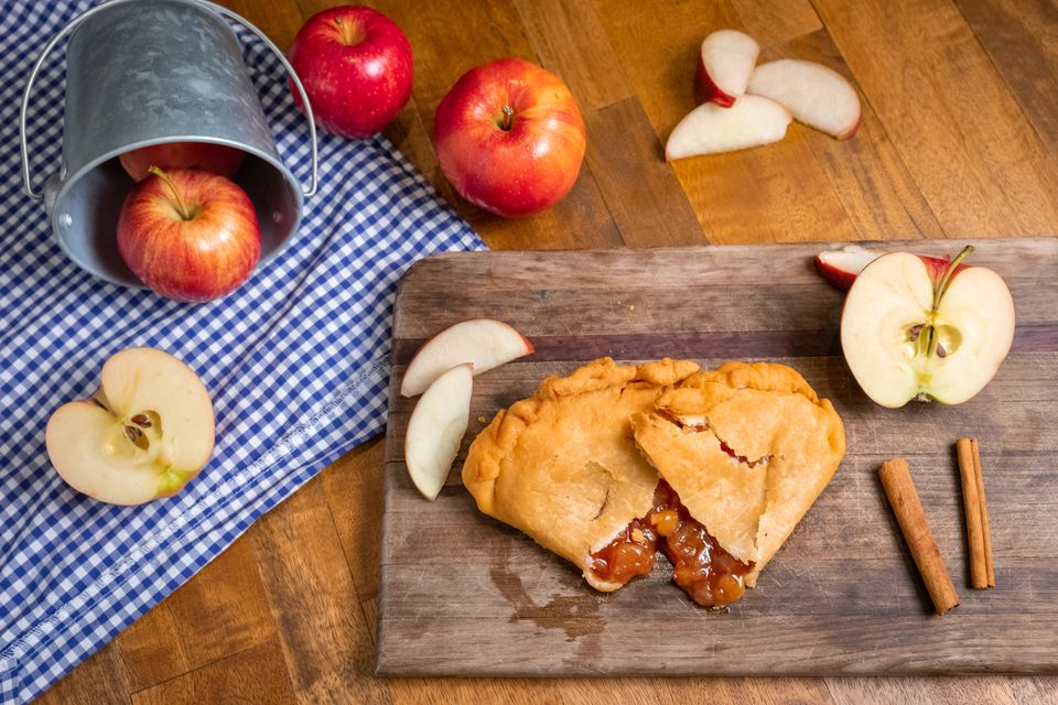 apple handpie on a cutting board with sliced and whole apples