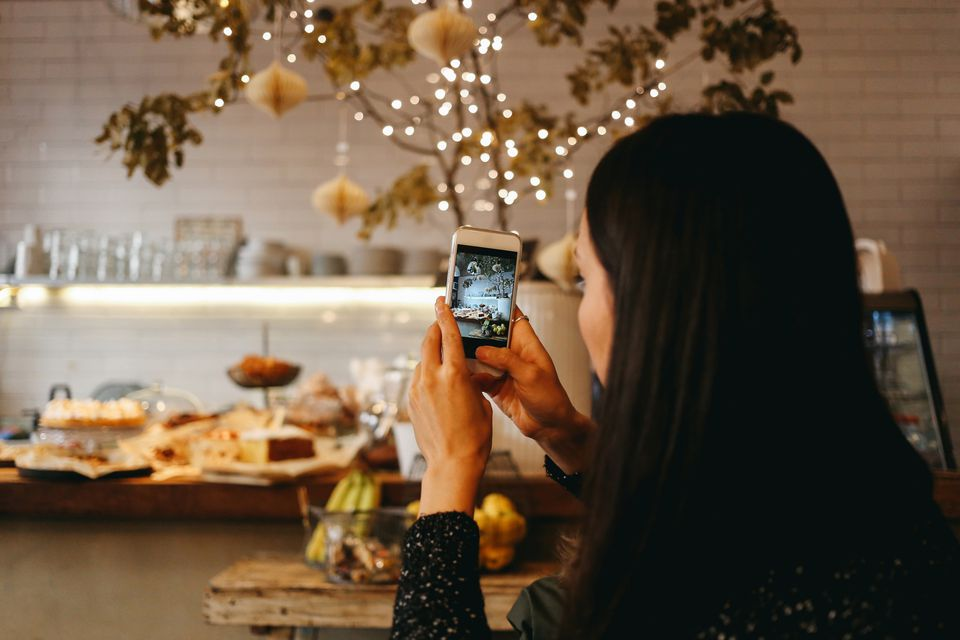 Person taking a photo of food with a smartphone
