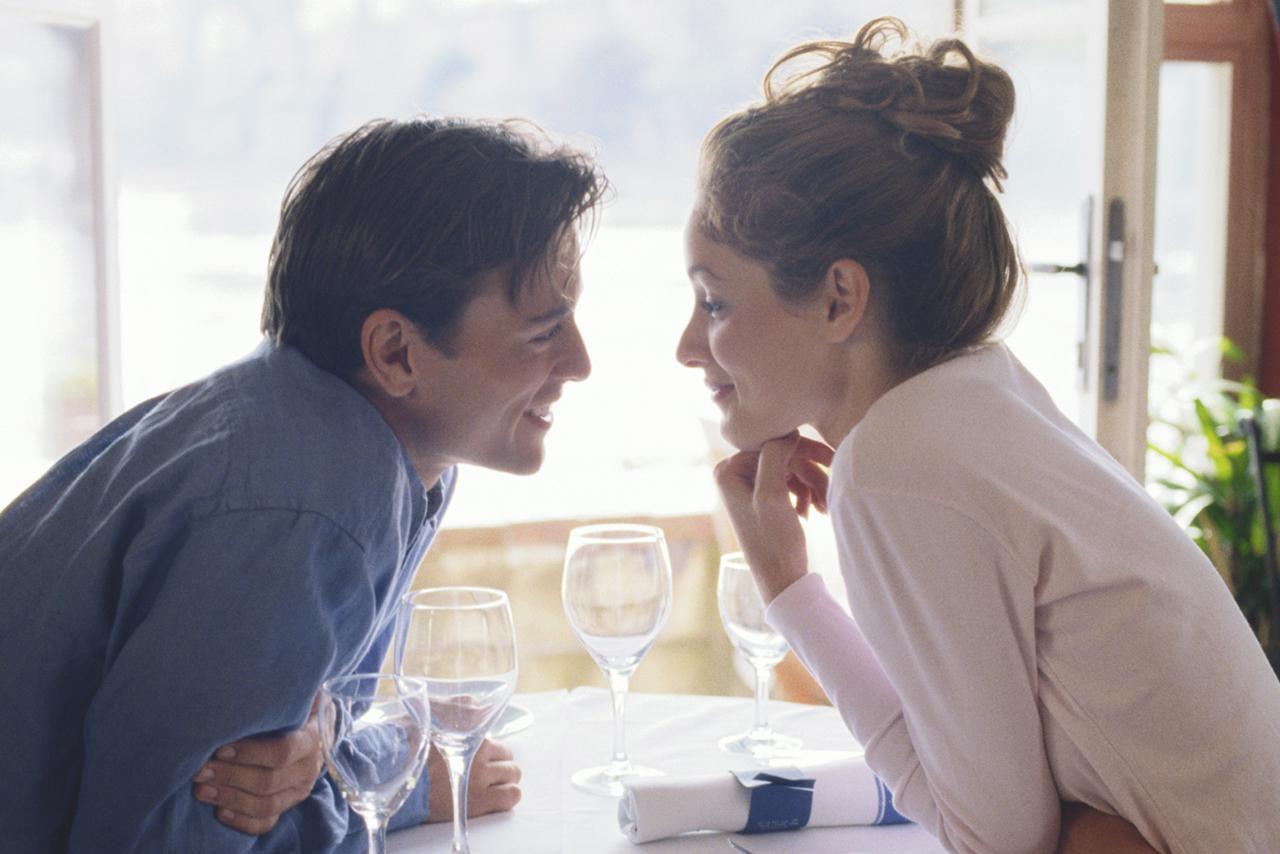 Pareja joven mirándose a los ojos a través de la mesa en la cafetería
