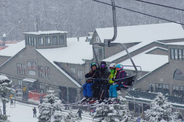 A family on a ski lift with the resort in the background