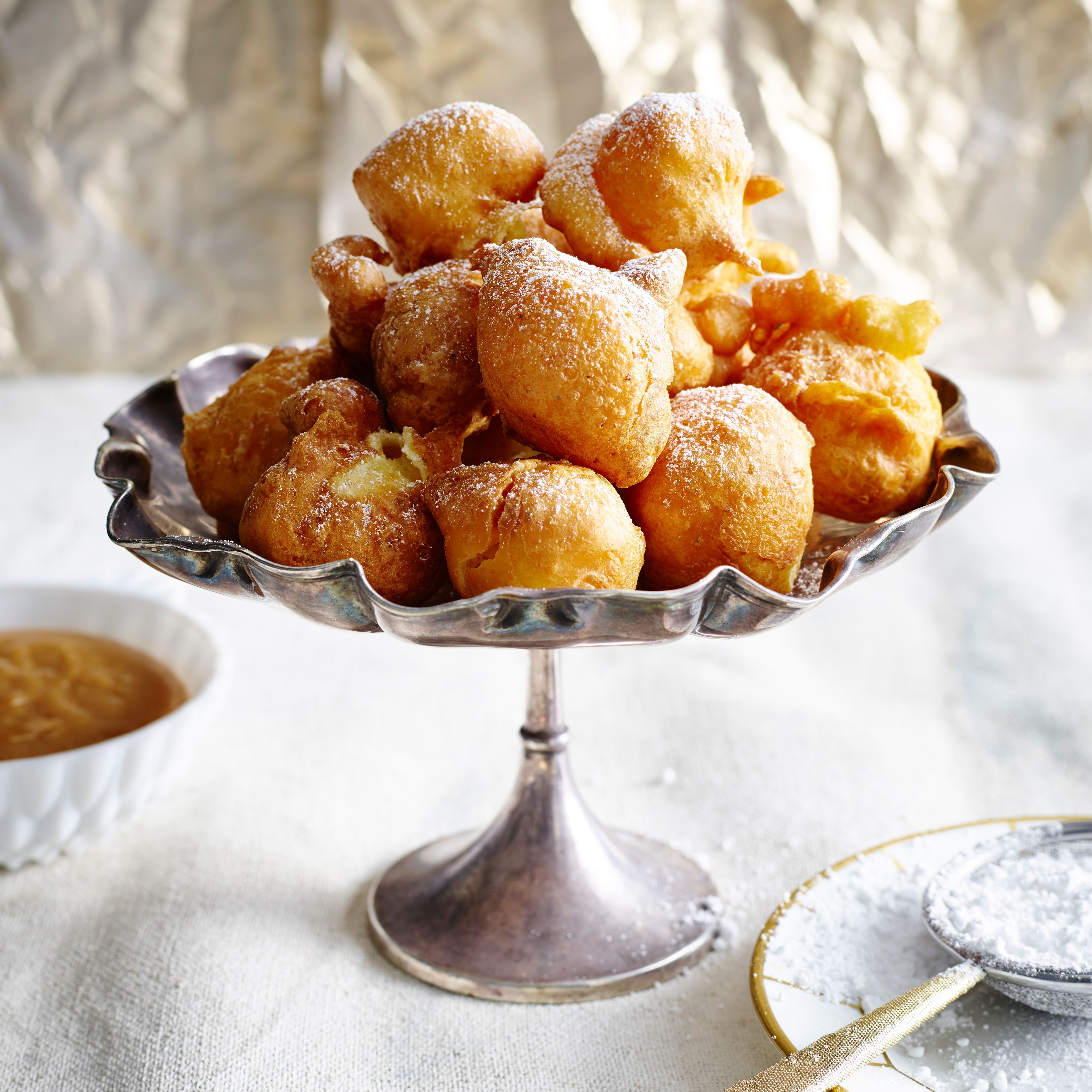 Bunuelos piled into silver serving dish dusted with icing sugar