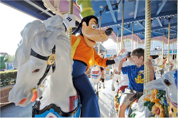 Goofy and small boy ride the merry go round at Disney World