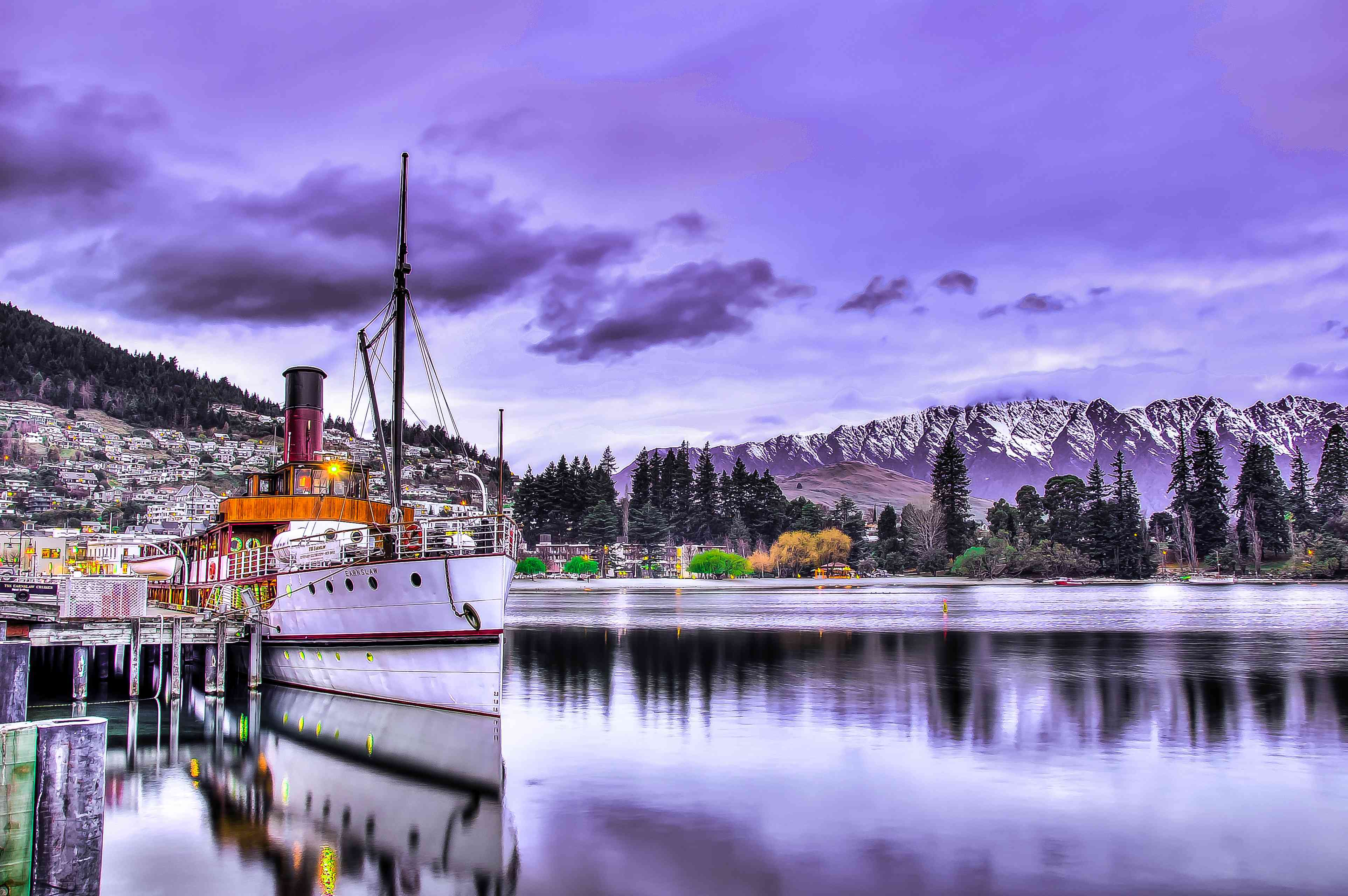 purple sunset sky with steamship on a lake in front of a town and snow-capped mountains