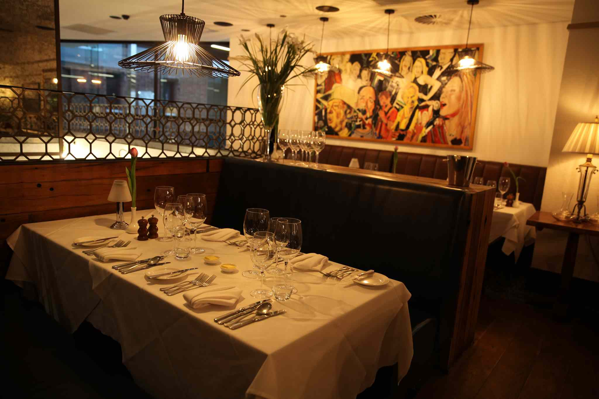 Dining room at Friends restaurant with white linen and artwork
