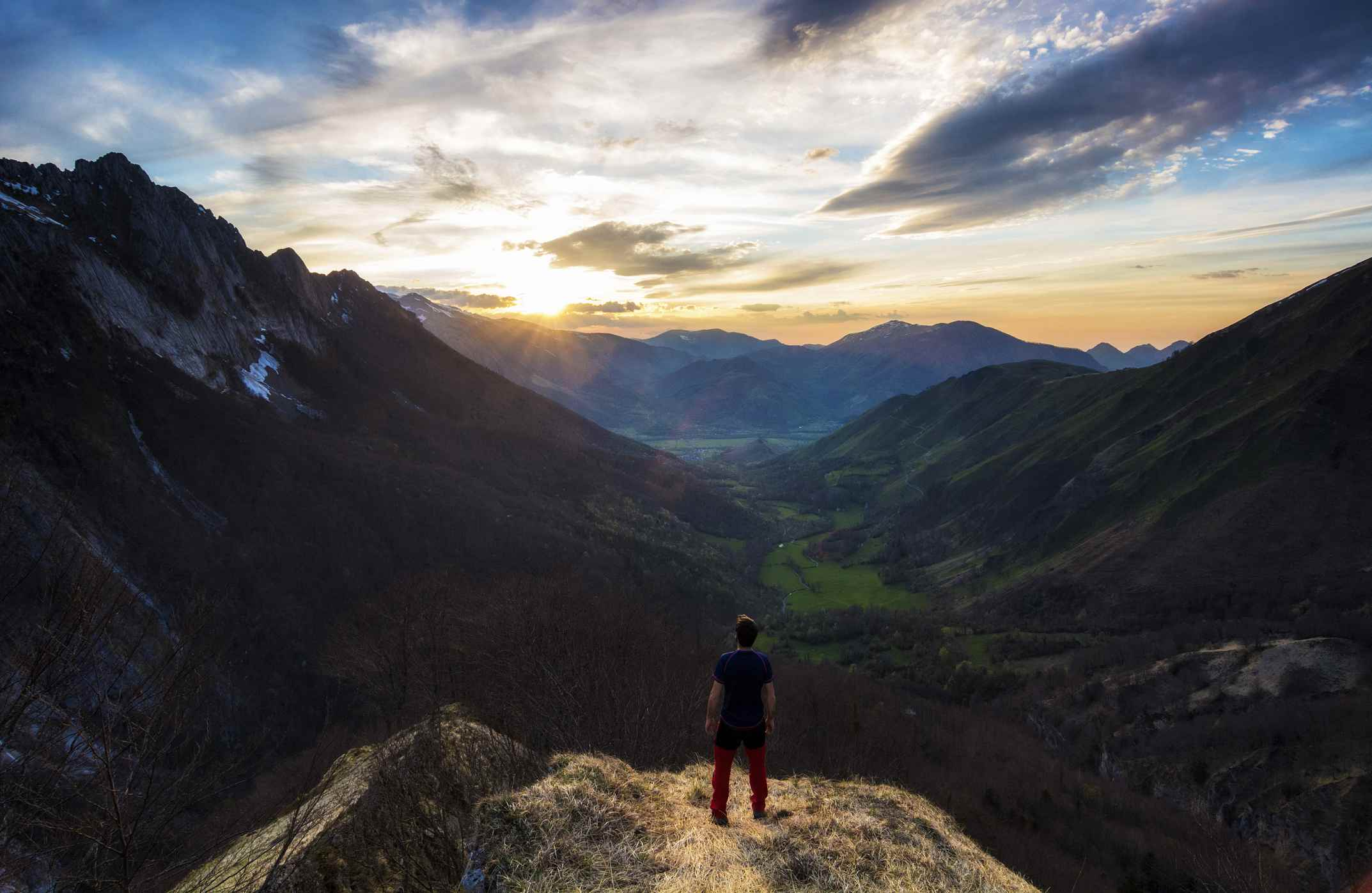 A man stands on a hill and looks out over a valley at sunset