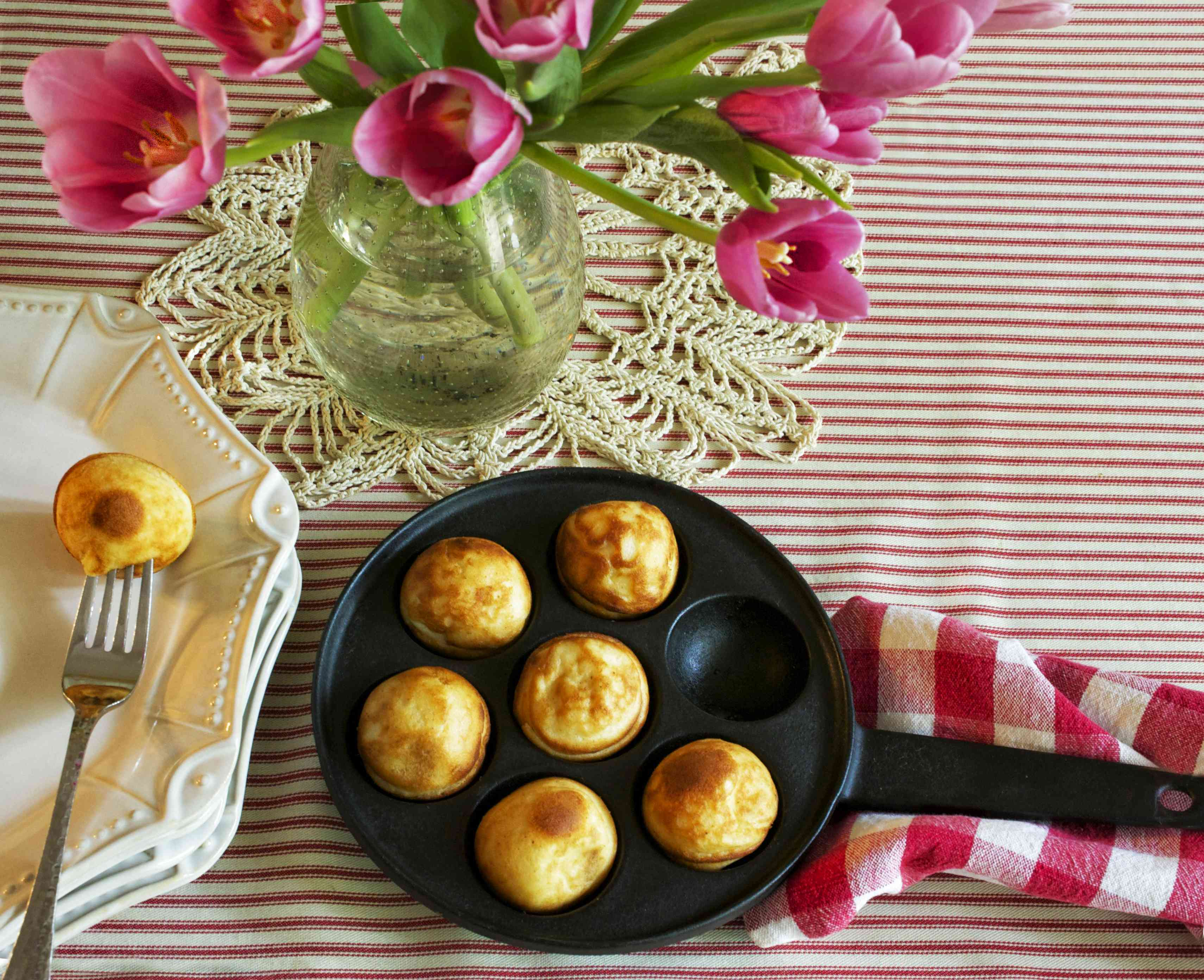 Round pancake balls in a special pan on a red and white table cloth