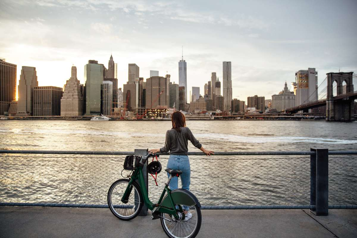 A woman stands alongside her bike overlooking the New York City skyline across the Hudson River