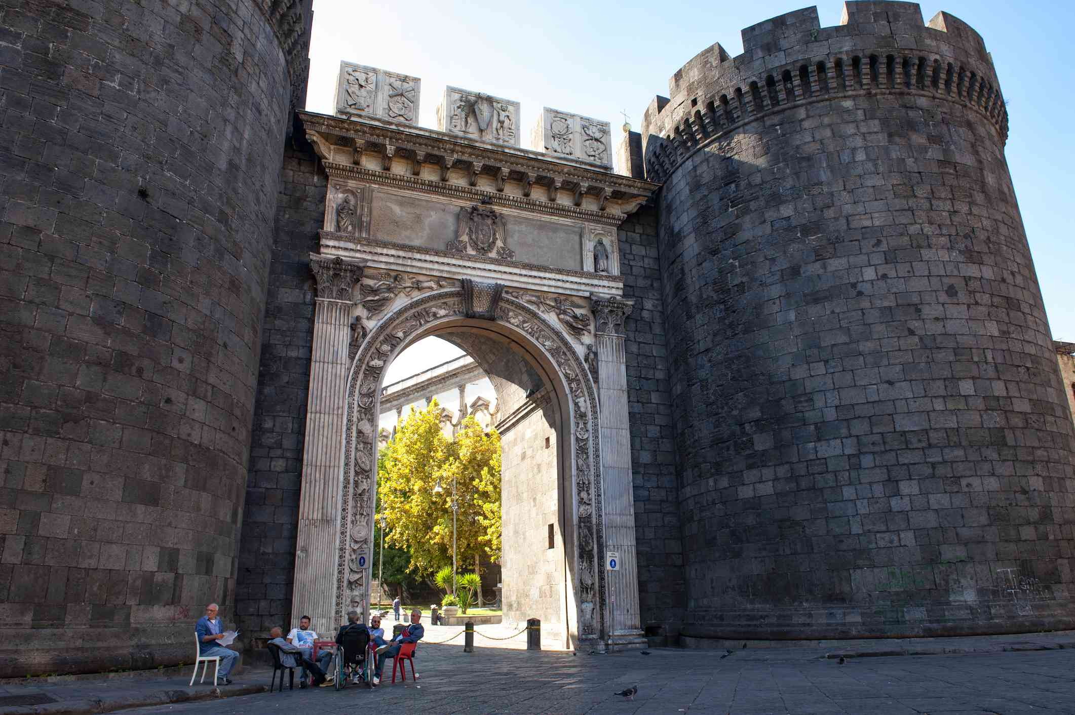 A group of men play cards in the shade of Porta Capuana