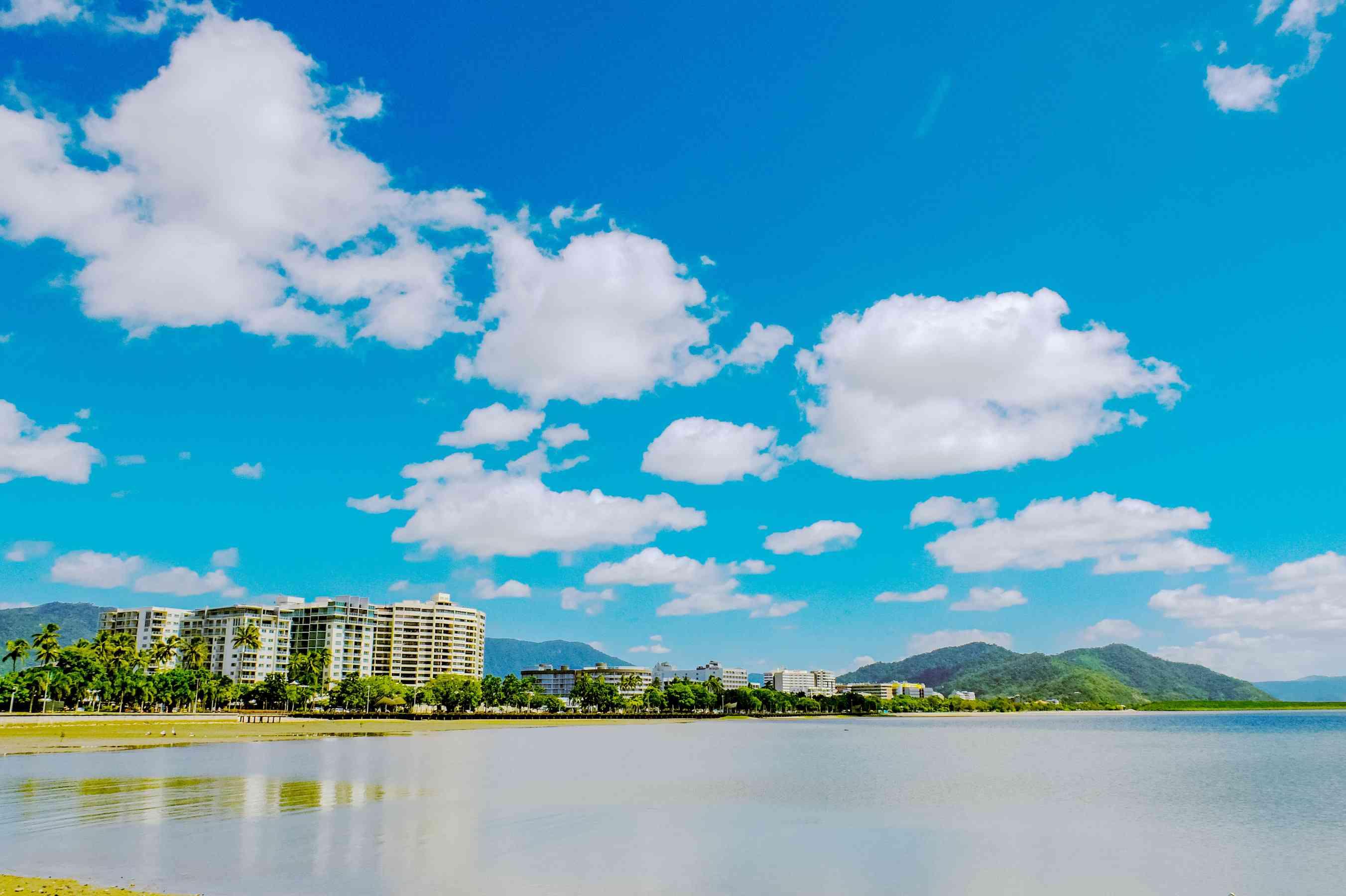 Vista de la playa con rascacielos y montañas sin el fondo de un cielo azul con nubes