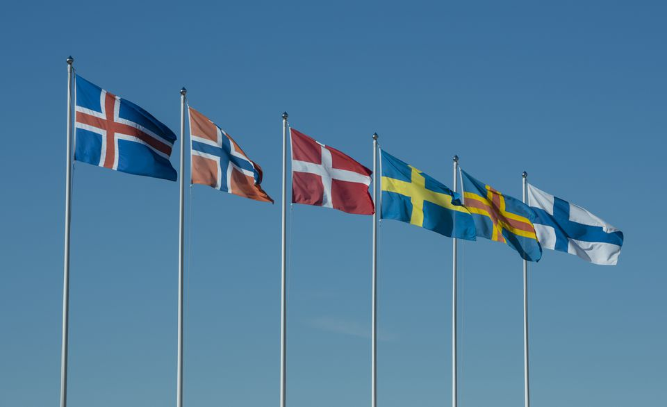 Row of Scandinavian national flags in front of blue sky