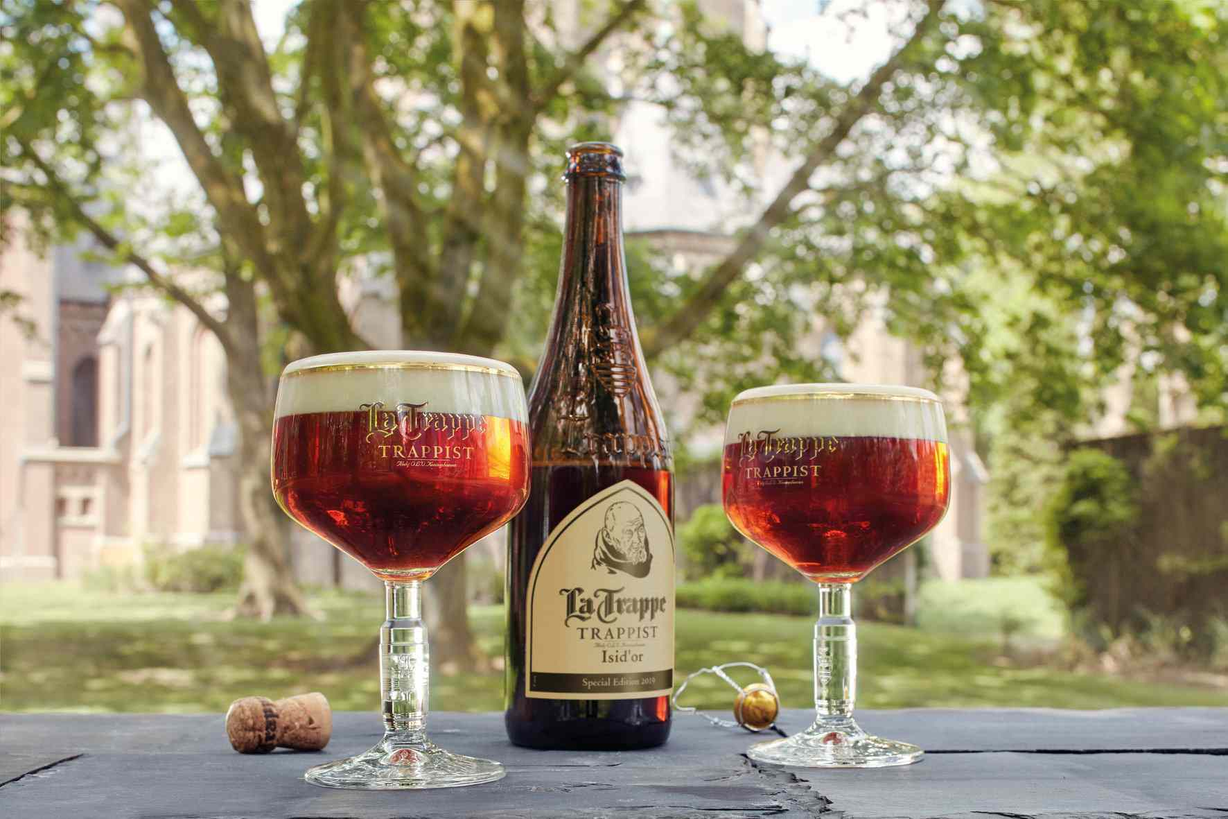 Two full goblets of beer and a bottle of La Trappe Trappis beer on a table with the abbey in the background