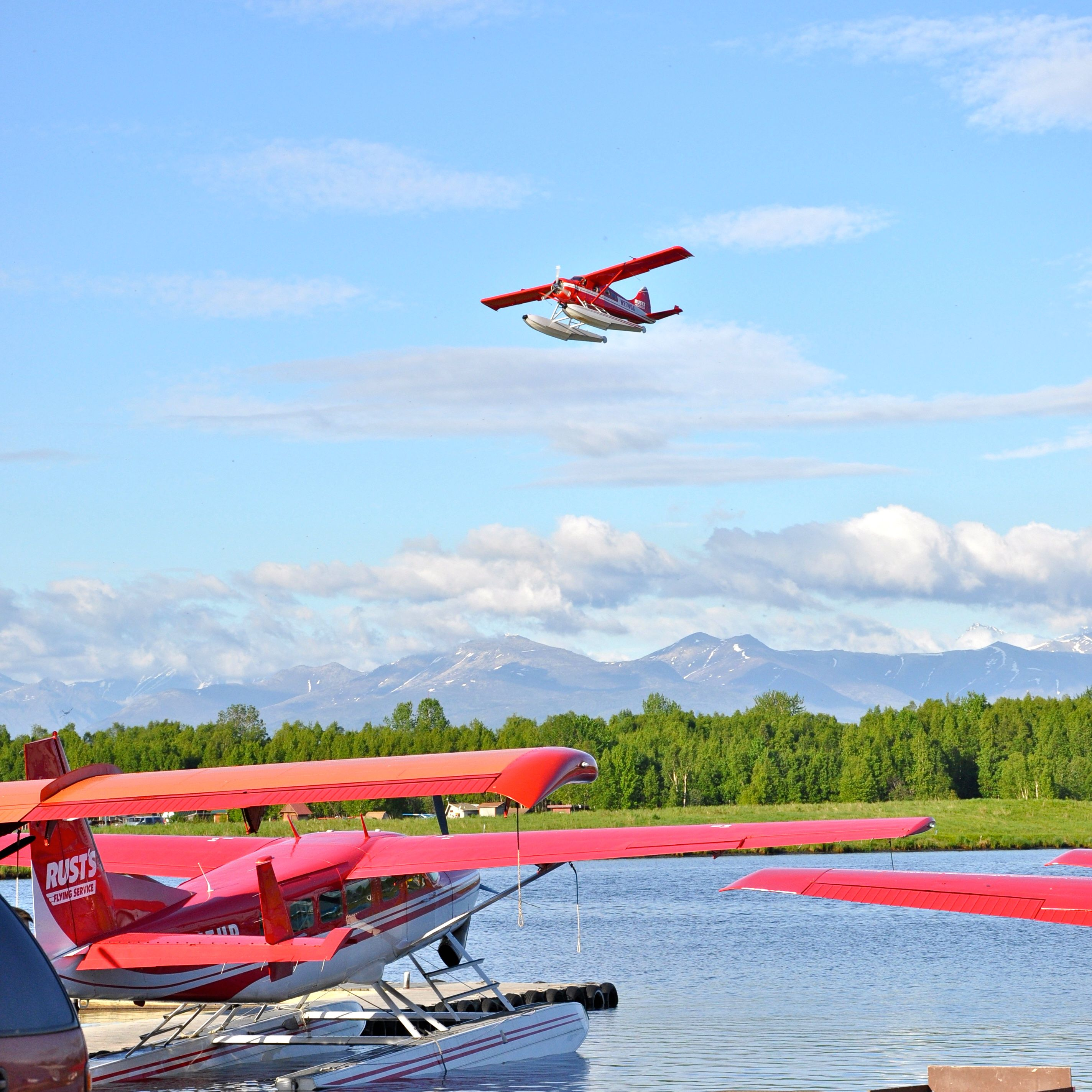 Plane preparing to land on lake containing other planes.