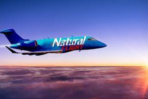 Natural Flight jet flying across sunsetting sky