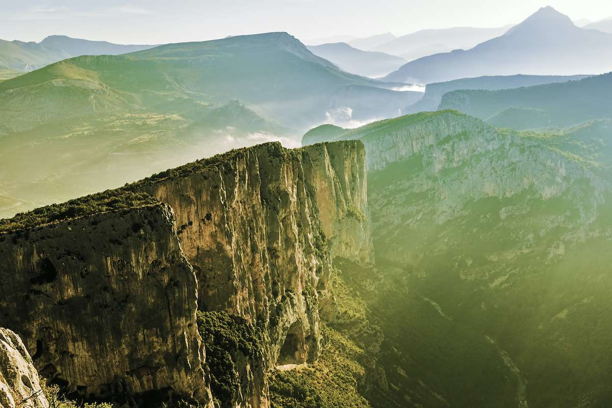 Rocky cliffs stretch into the distance along a flowing river below.