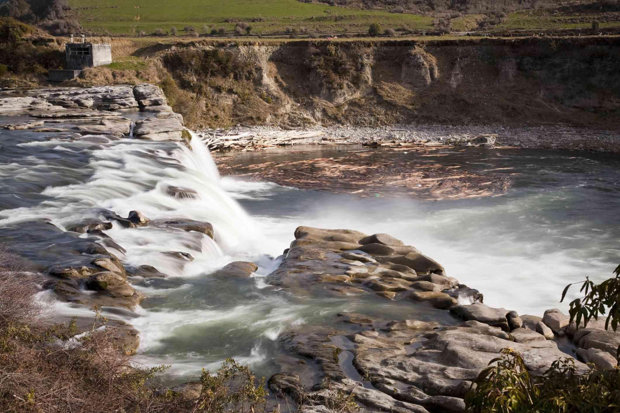 water falling in a short waterfall on a rocky riverbank