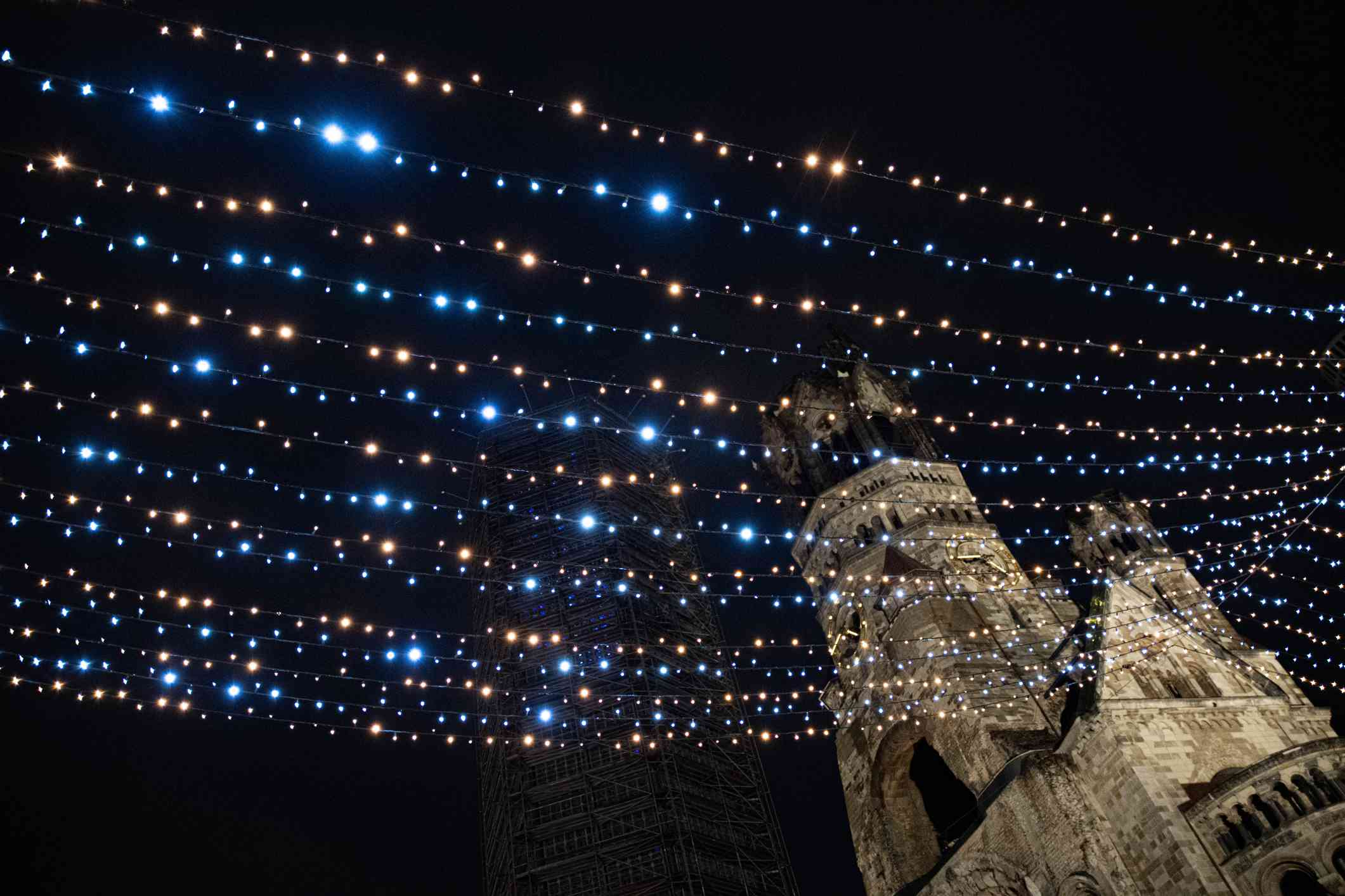 Rows of glowing golden and blue Christmas lights in night sky over blurry building silhouette of Kaiser Wilhelm church named Gedächtniskirche in German language. Cathedral on Breitscheidplatz in Berlin. Kaiser Wilhelm memorial church