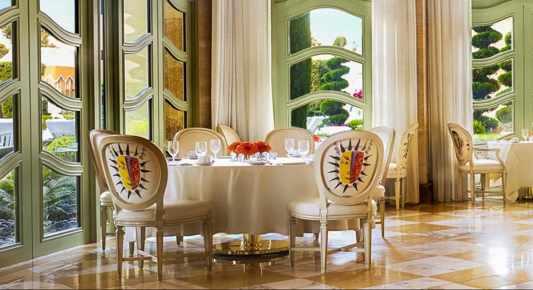 White table setting and chairs with colorful masks painted on the back