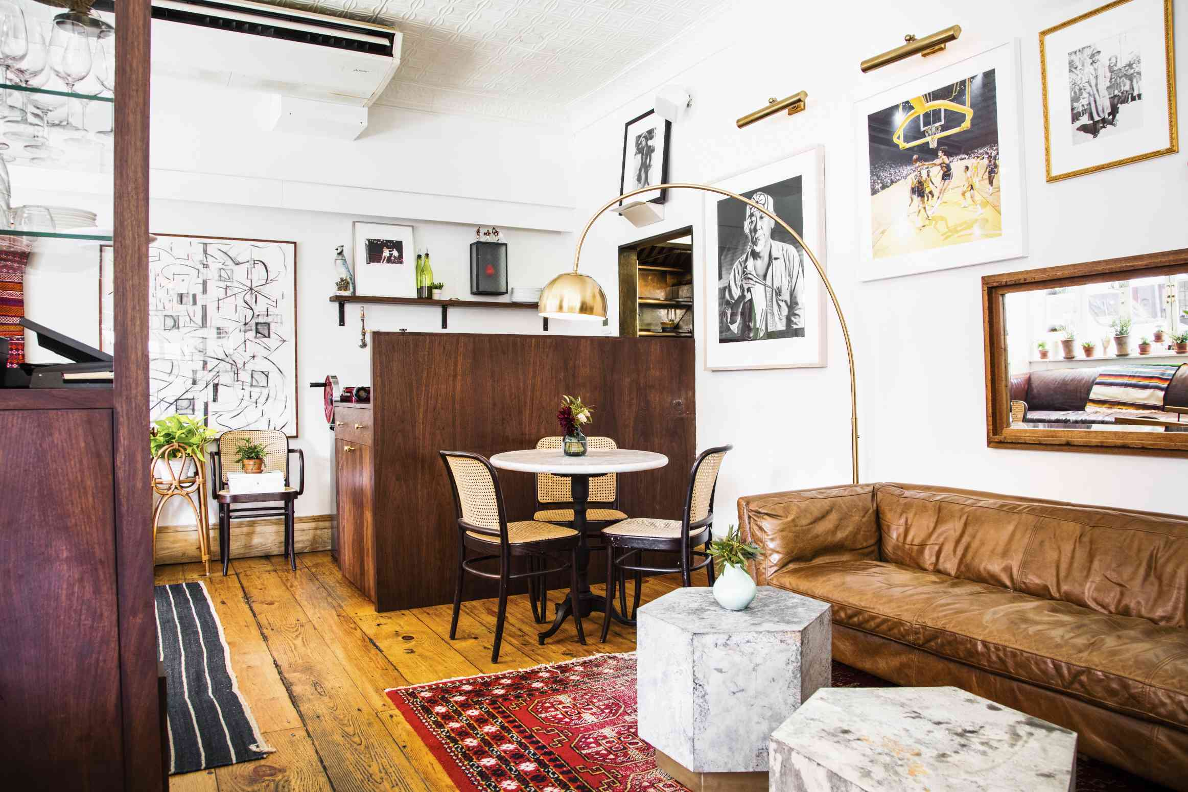 Room with a leather couch, small table with three chairs, area rug, wall hangings, and coffee tables