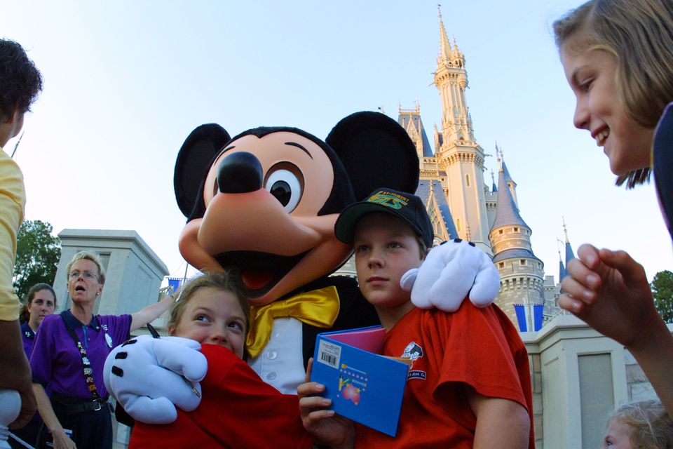 The Walt Disney character Mickey Mouse greets children at Magic Kingdom November 11, 2001 in Orlando, Florida