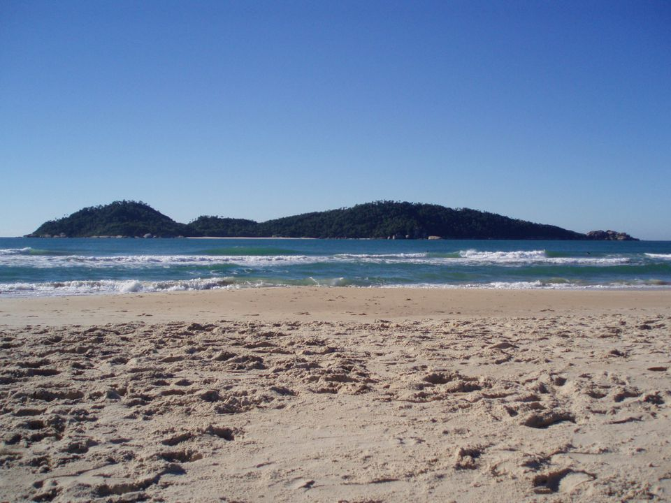 A clean, sandy beach with blue waves