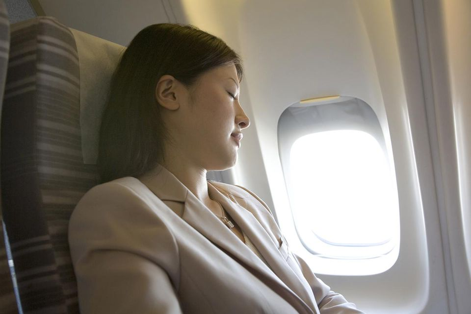 Young woman sleeping on airplane, side view