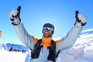 Man with thumbs up on top snow mountain
