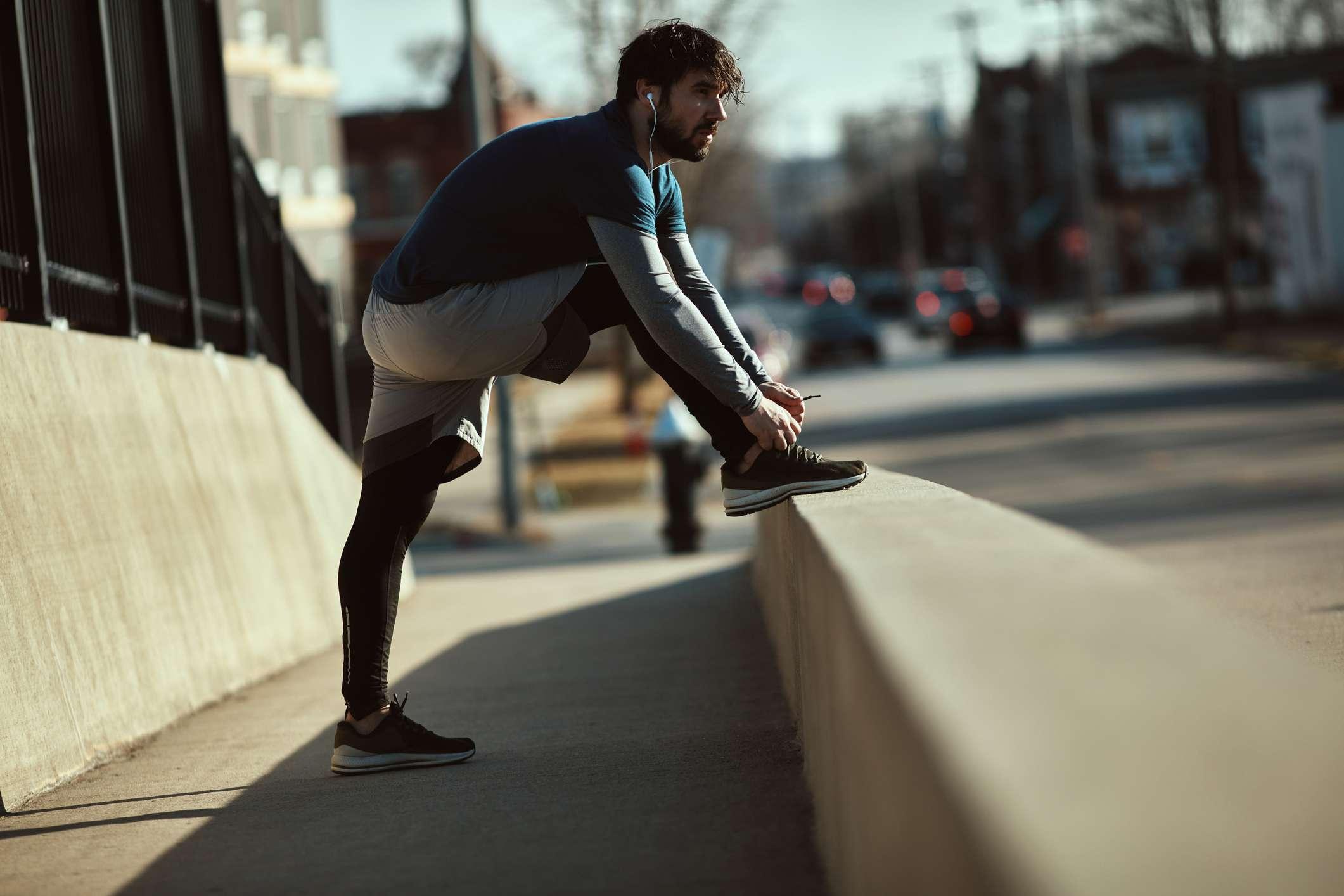 Man stretching on street