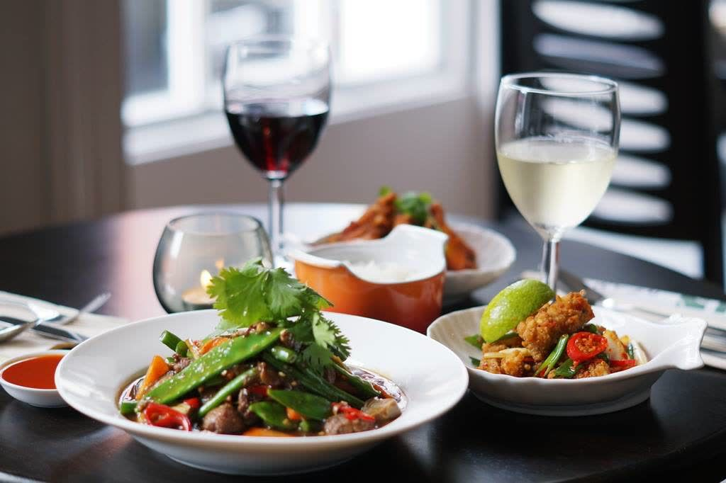 asian food on white plates with two glasses of wine