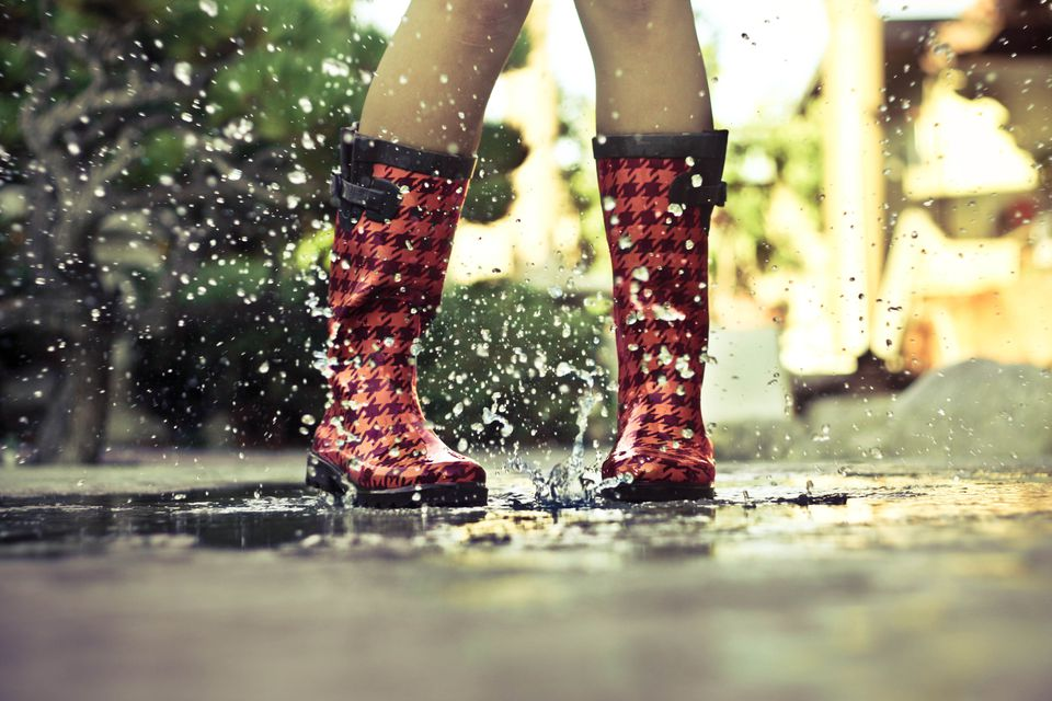 Girl wearing rainboots in a puddle