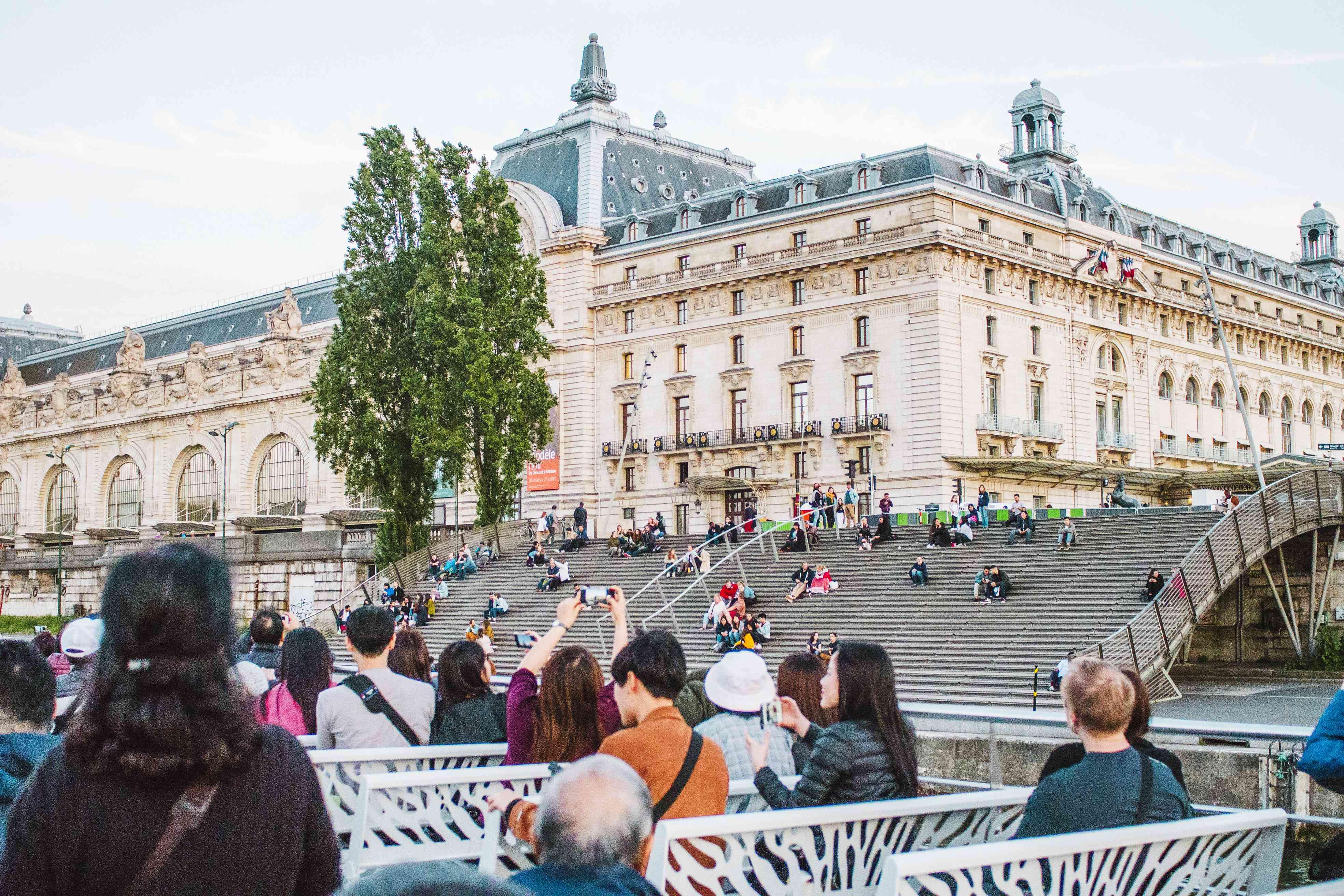 Gente sentada en las escaleras junto al río Sena