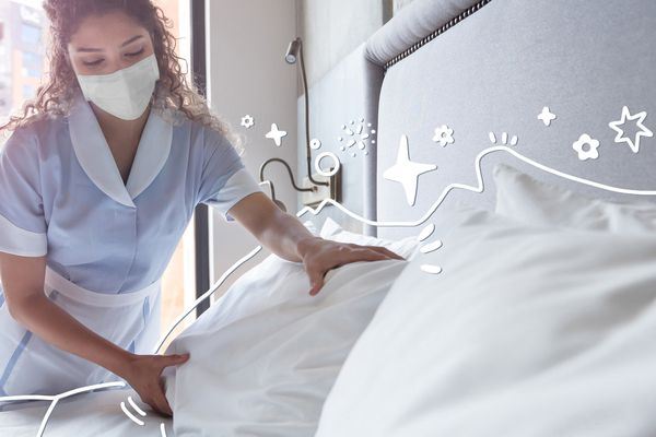 A maid cleaning a hotel room with a mask on