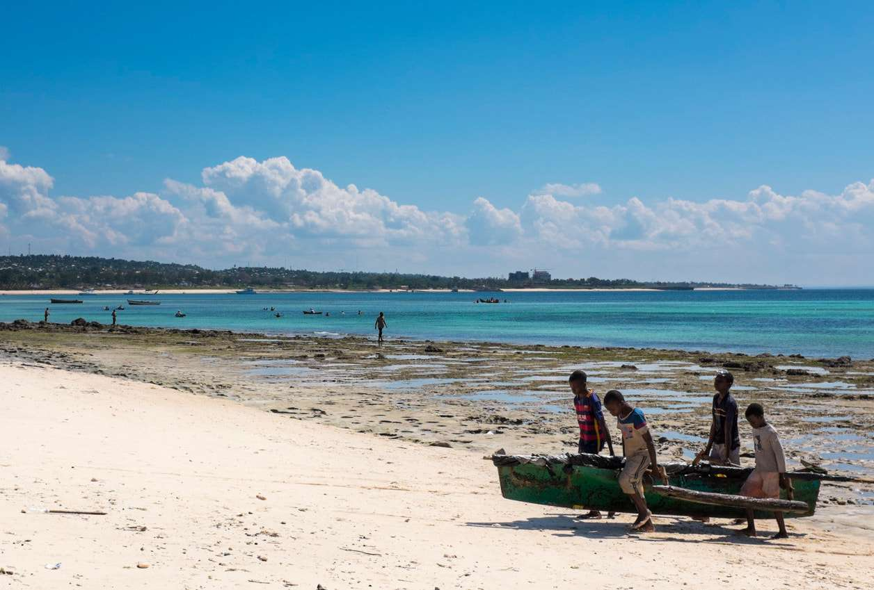 Boys carry a fishing boat up Wimbe Beach in Pemba, Mozambique
