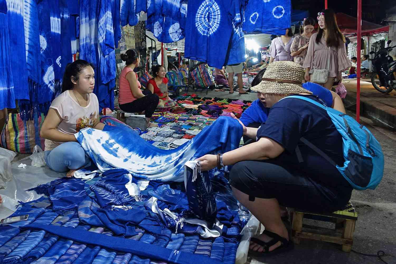 Tourists browsing indigo-dyed cloth in Night Market, Luang Prabang