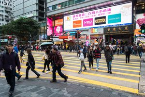 People walking across Nathan Road with Chungking Mansions entrance in the background, a famous complex building with cheap hotels and shops, Hong Kong, Tsim Sha Tsui