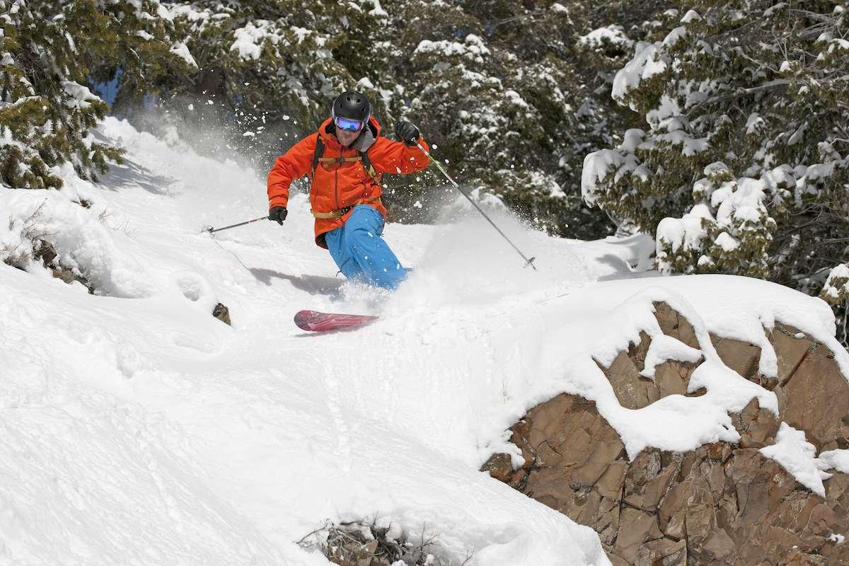 A man skis through deep snow along a rocky forest trail
