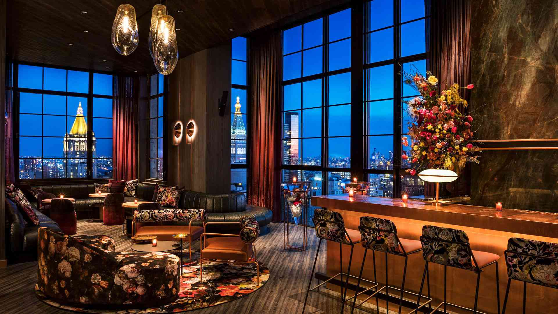 The Fleur Room at the Moxy in manhattan with lounge chairs and seating and a view of manhattan at Twilight