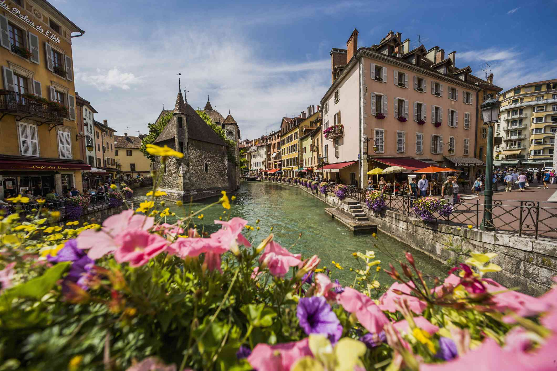 Palais (palace) de l'Ile and Thiou river with colorful flowers in the foreground