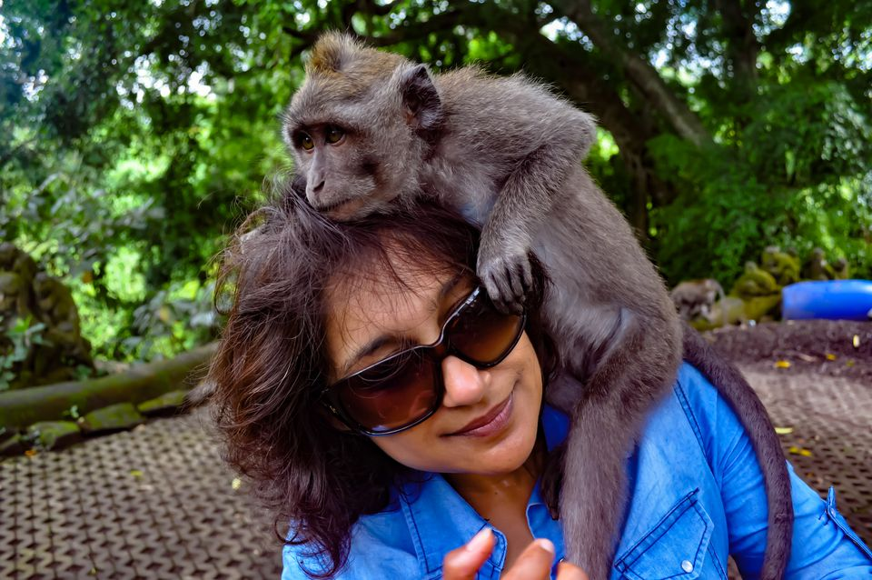 A monkey climbs on a woman