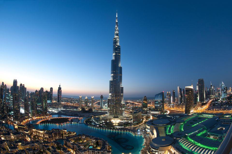 Burj khalifa skyscraper towering above other modern buildings in dubai at dusl