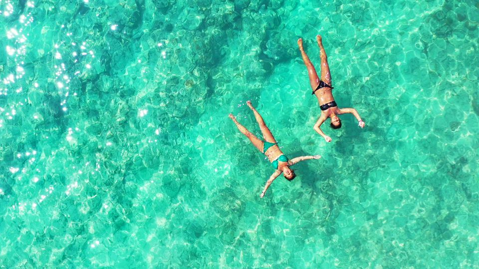 Women floating in crystal clear water