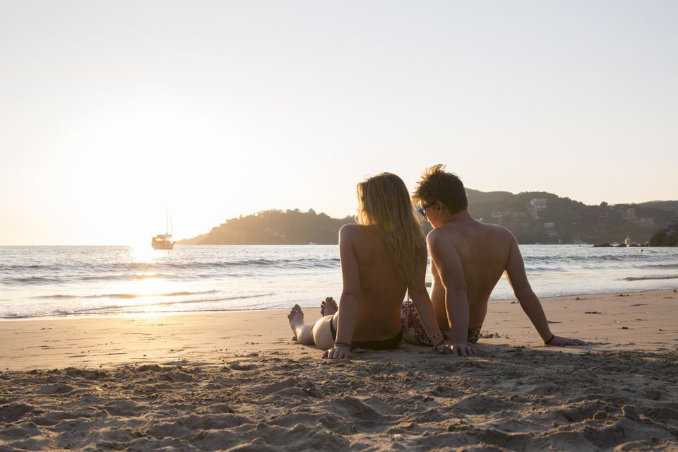 Young couple relax on beach, listen to music